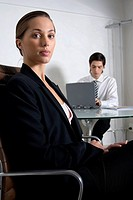 Portrait of a businesswoman sitting with a businessman working on a laptop in the background