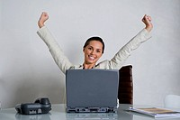 Portrait of a businesswoman smiling with her arms raised