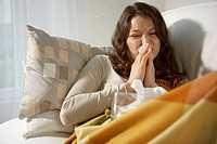 Close-up of a mid adult woman sneezing on the bed