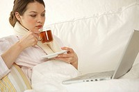 Mid adult woman drinking a cup of tea with a laptop on her lap (thumbnail)