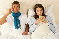 Portrait of a mid adult woman reclining with a mid adult man on the bed and drinking a cup of tea