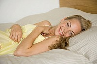 Portrait of a young woman lying on the bed and smiling