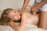 Young woman receiving back massage from a man