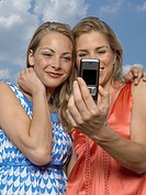 Close-up of two young women taking a picture of themselves with a mobile phone and smiling