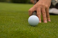Close-up of a man's hand aiming a golf ball