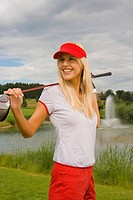 Side profile of a mid adult woman holding a golf club and smiling