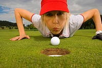 Portrait of a mid adult woman blowing a golf ball towards a hole (thumbnail)