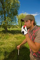 Side profile of a mid adult man holding a golf club and kissing a golf ball