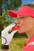 Close-up of a mid adult woman kissing a golf ball