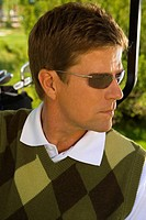 Close-up of a mid adult man in a golf cart