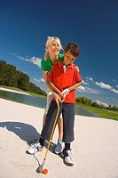 Mid adult woman giving golf training to his son