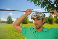 Close-up of a mid adult man holding a golf club over his head