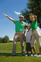 Mid adult couple with their son standing on a golf course