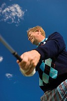 Low angle view of a mid adult man swinging a golf club and smiling