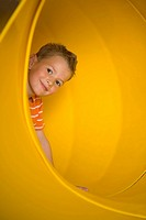 Portrait of a boy in a tubular slide and grinning