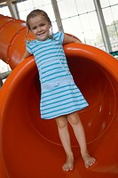 Portrait of a girl standing on a tubular slide and smiling