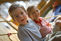 Portrait of a boy sitting with his friend on a rope climbing net