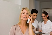 Businesswoman talking on a cordless phone with two business executives discussing in the background