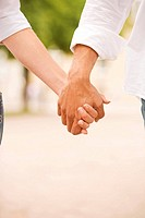 Close-up of a man and a woman holding each other's hands