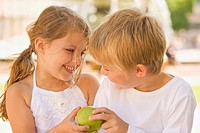 Close-up of a boy and a girl holding a green apple