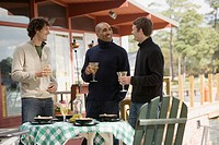 Men with wine chatting over meal outdoors