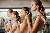Side profile of four young women exercising with dumbbells