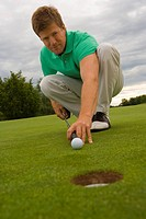 Portrait of a mid adult man putting a golf ball into a hole