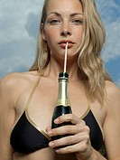 Portrait of a young woman drinking beer with a drinking straw