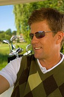 Close-up of a mid adult man in a golf cart and smiling