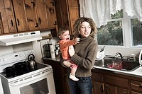 Woman, standing in her kitchen, holding her young daughter