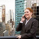 Businesswoman on cell phone overlooking city
