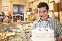 Young man in bakery, holding layer cake, smiling, portrait
