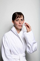 Woman wearing bathrobe holding thermometer in mouth