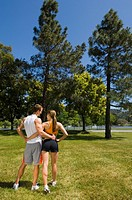 Couple in sportswear walking in park, rear view
