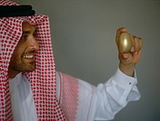 Arab man holding golden egg
