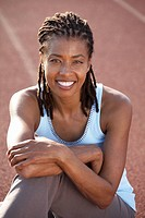 Woman sitting on track at track and field stadium, smiling, portrait