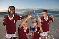 Four boys 10-11,12-13 in football strips holding trophy on beach
