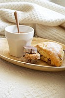 Pastries and cup of tea on wooden tray on blanket, close-up