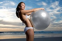 Young woman holding large exercise ball on beach