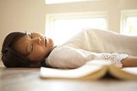 Woman sleeping beside book on living room floor