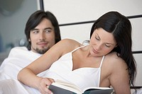 Man and woman relaxing on bed, reading