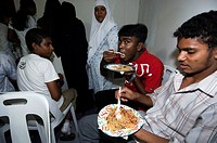 Male, guests on Saufa Ibrahim and Mohamed Misdhath wedding party are eating a rice dish from plastic plates