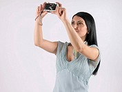 Woman holding up camera to take pictures