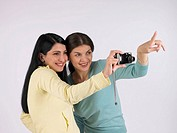 Female friends taking pictures with a camera (thumbnail)