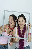 Two young female friends holding up picture frame, smiling at camera, portrait