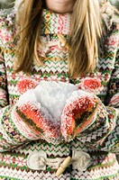 Young woman with handful of snow, close-up, mid section