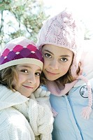 Two sisters smiling at camera, cheek to cheek, both wearing knit hats, portrait