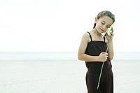 Girl standing on beach, holding flower up to cheek, eyes closed, smiling