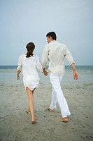 Father and daughter walking hand in hand on beach, rear view, full length
