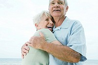 Senior couple hugging, woman laughing, low angle view
